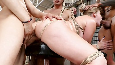 Submissive Lisey Charming offers up her body around a group of Doms